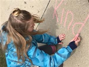 student writing be kind in chalk